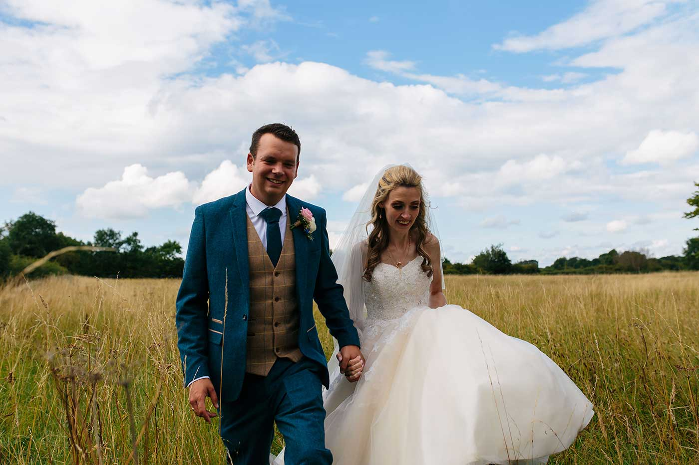 couples portrait walking in a field