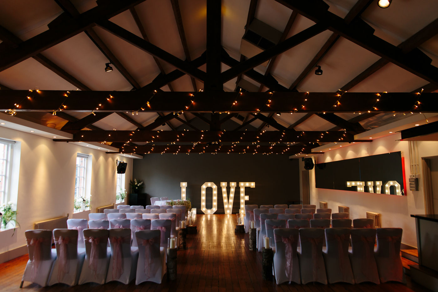 the castlefield rooms ceremony room wit love letters and rustic oak beams covered in fairy lights