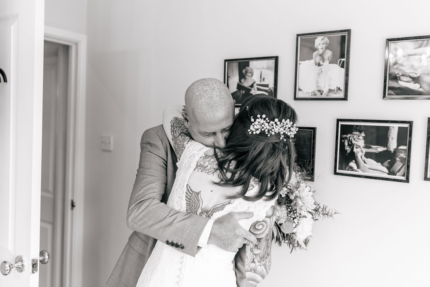 bride giving her dad a huge hug at home as he sees her for the first time in the wedding dress
