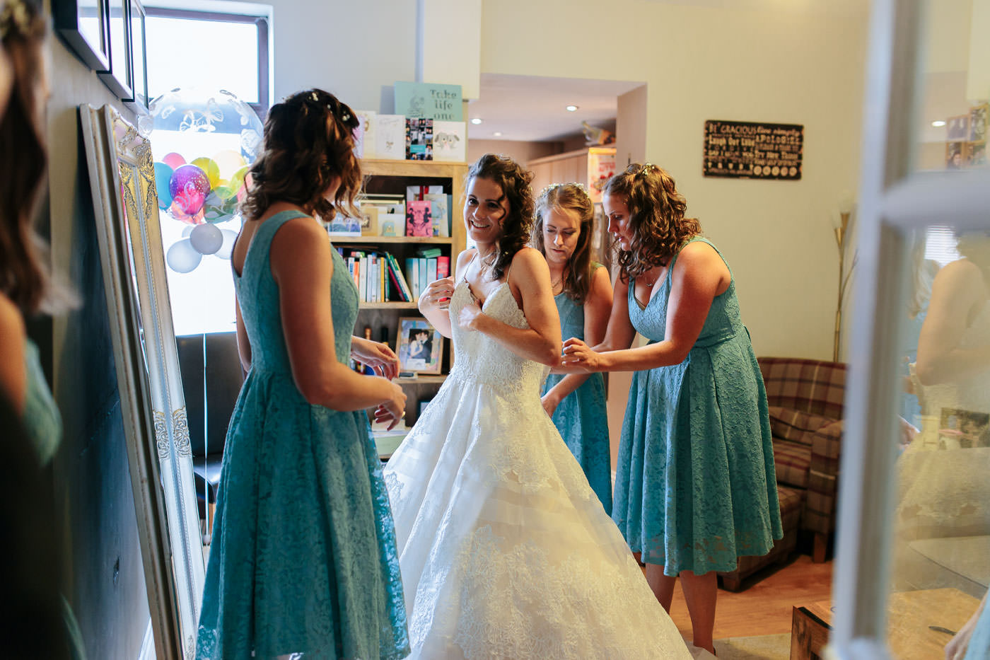 bridesmaids helping lucy into her dress