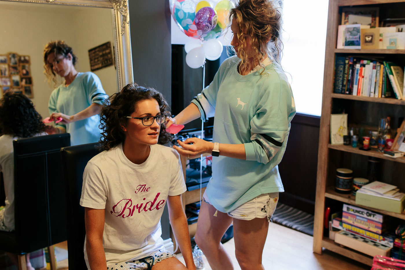 lucy having hair done by bridesmaid