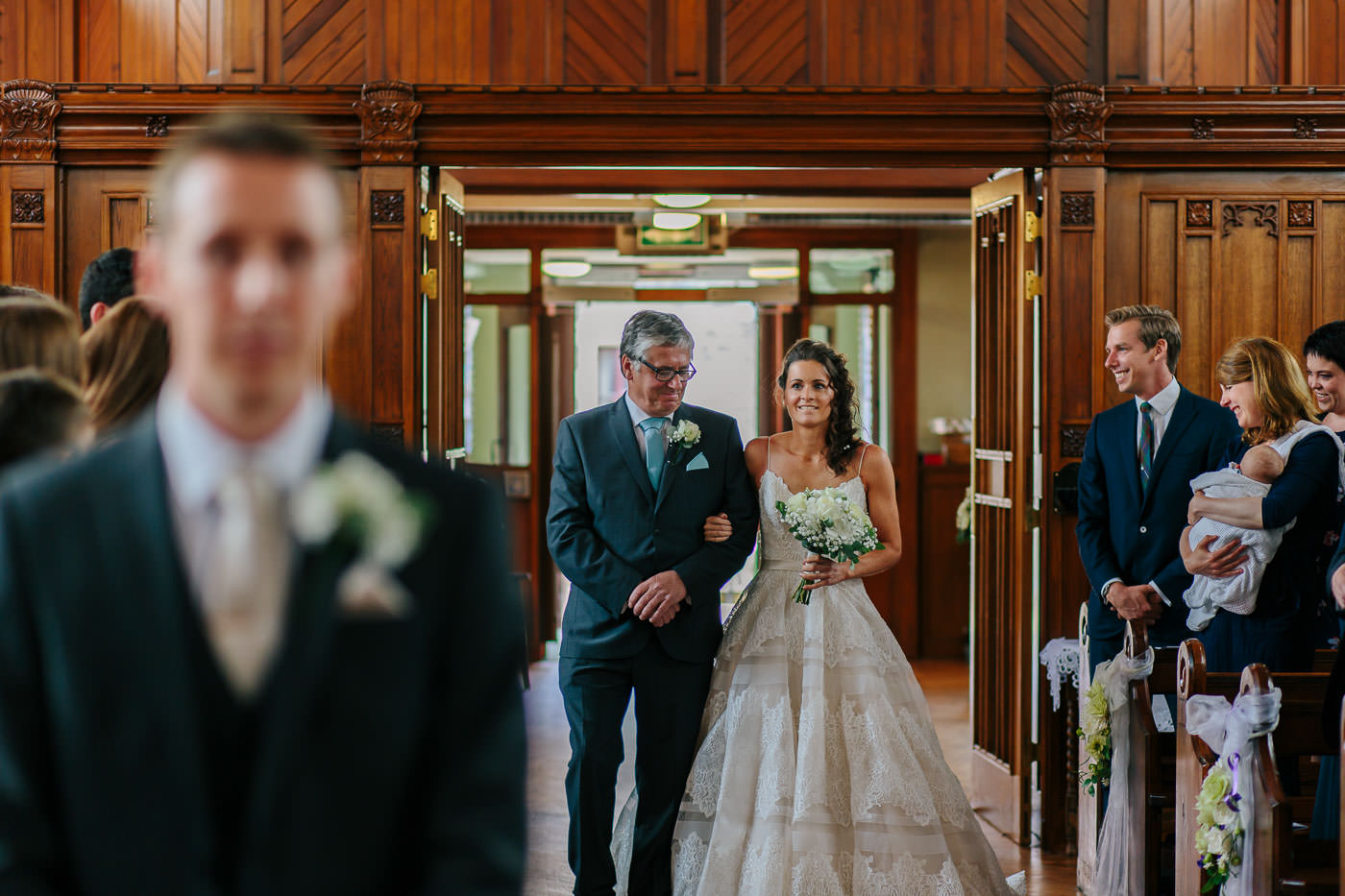 bride walking down the aisle in church with her farther