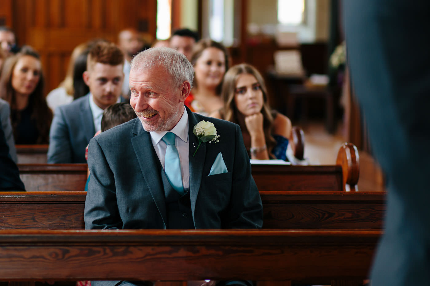 groomsman smiling during the church wedding ceremony