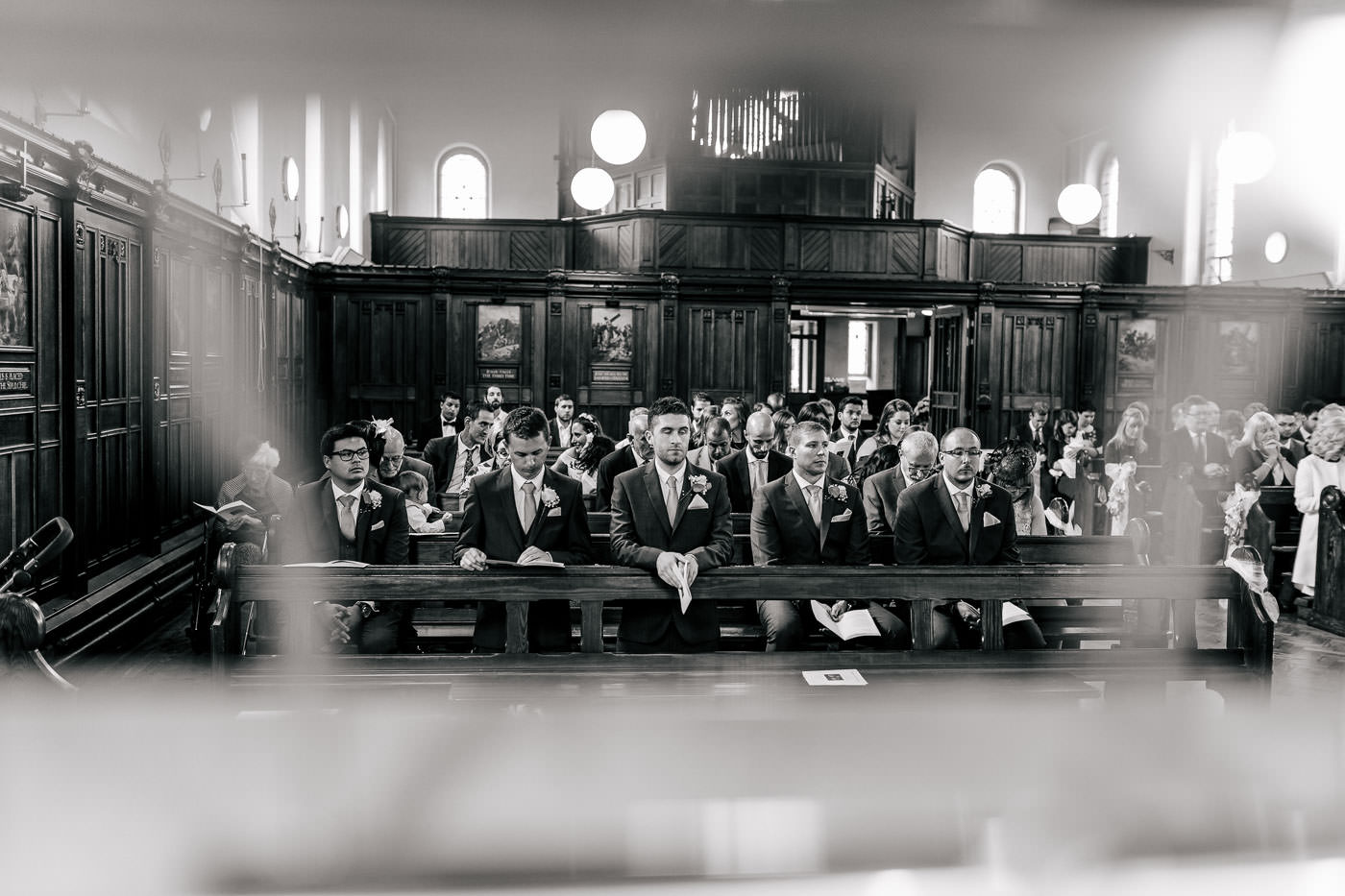 groomsmen sat at the front of church during the wedding ceremony