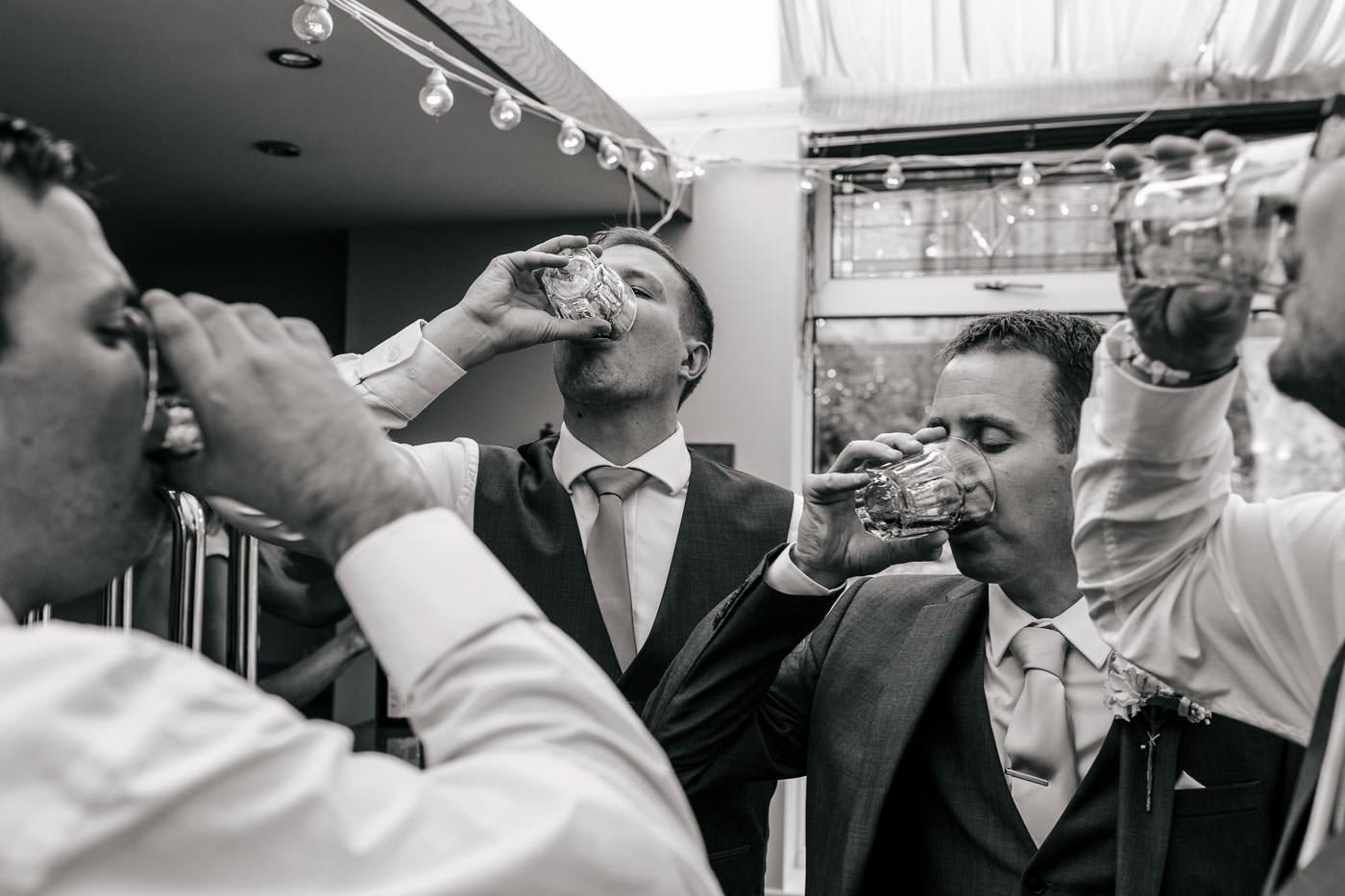 groomsmen drinking shots at the bar