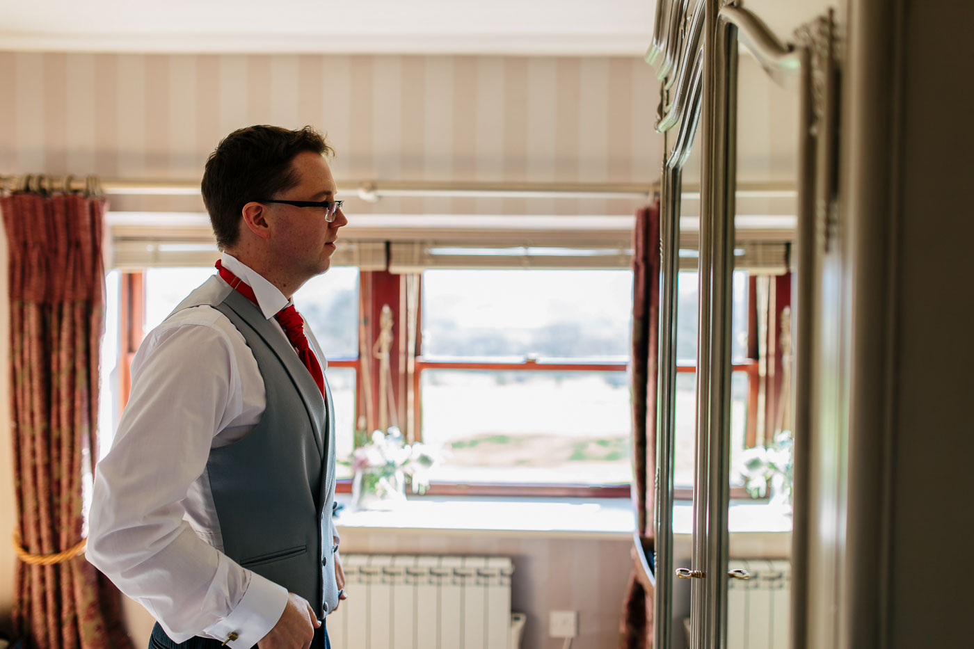 groom looking in the mirror at The Shireburn Arms Hotel