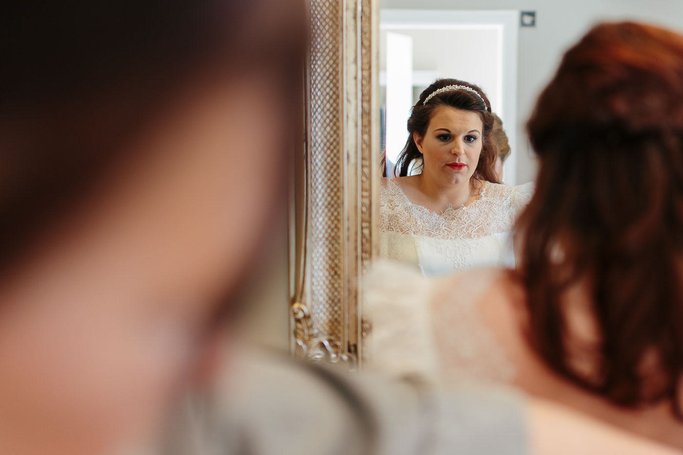 bride looking in the mirror at shireburn arms wedding