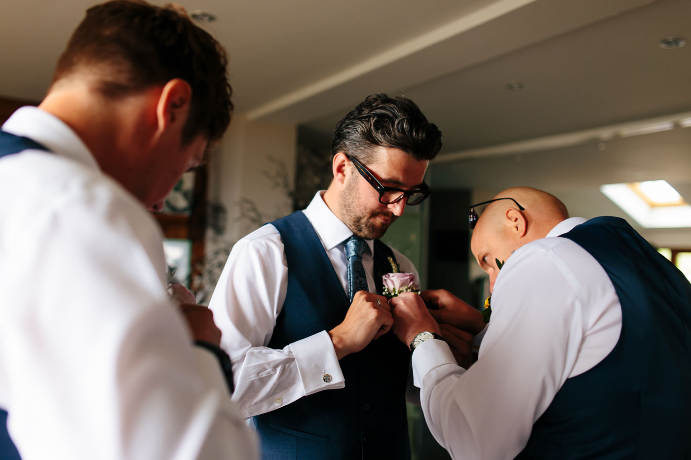 groom helping best man with buttonhole