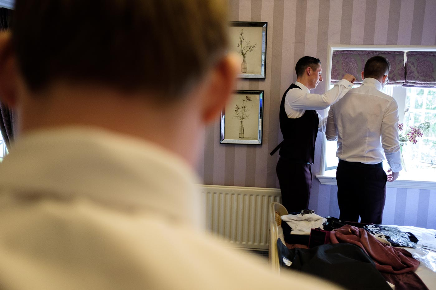 groomsman helping the groom get ready