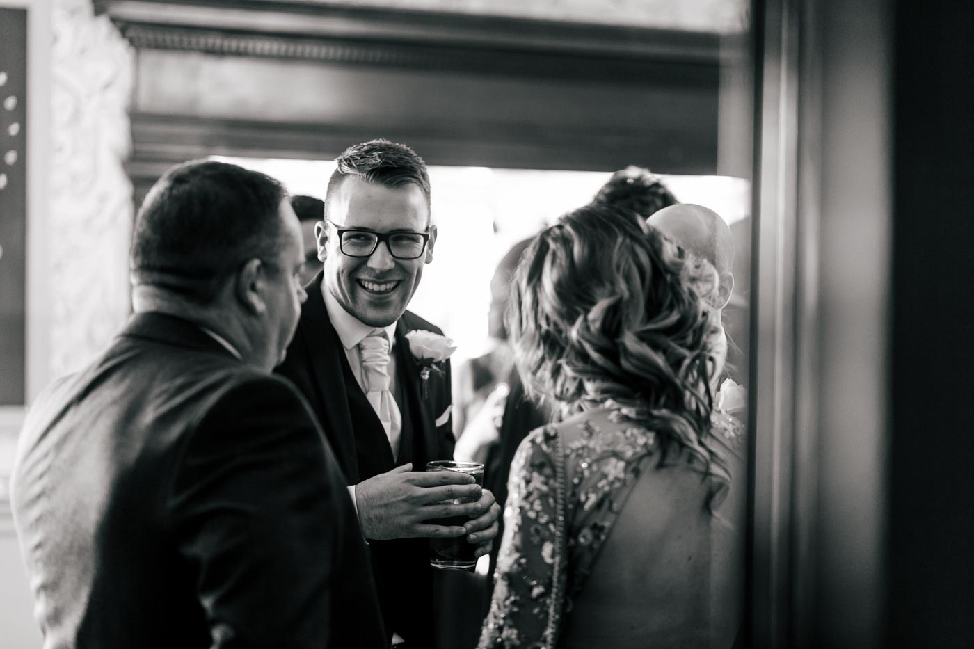 candid photograph of the groom speaking with guests