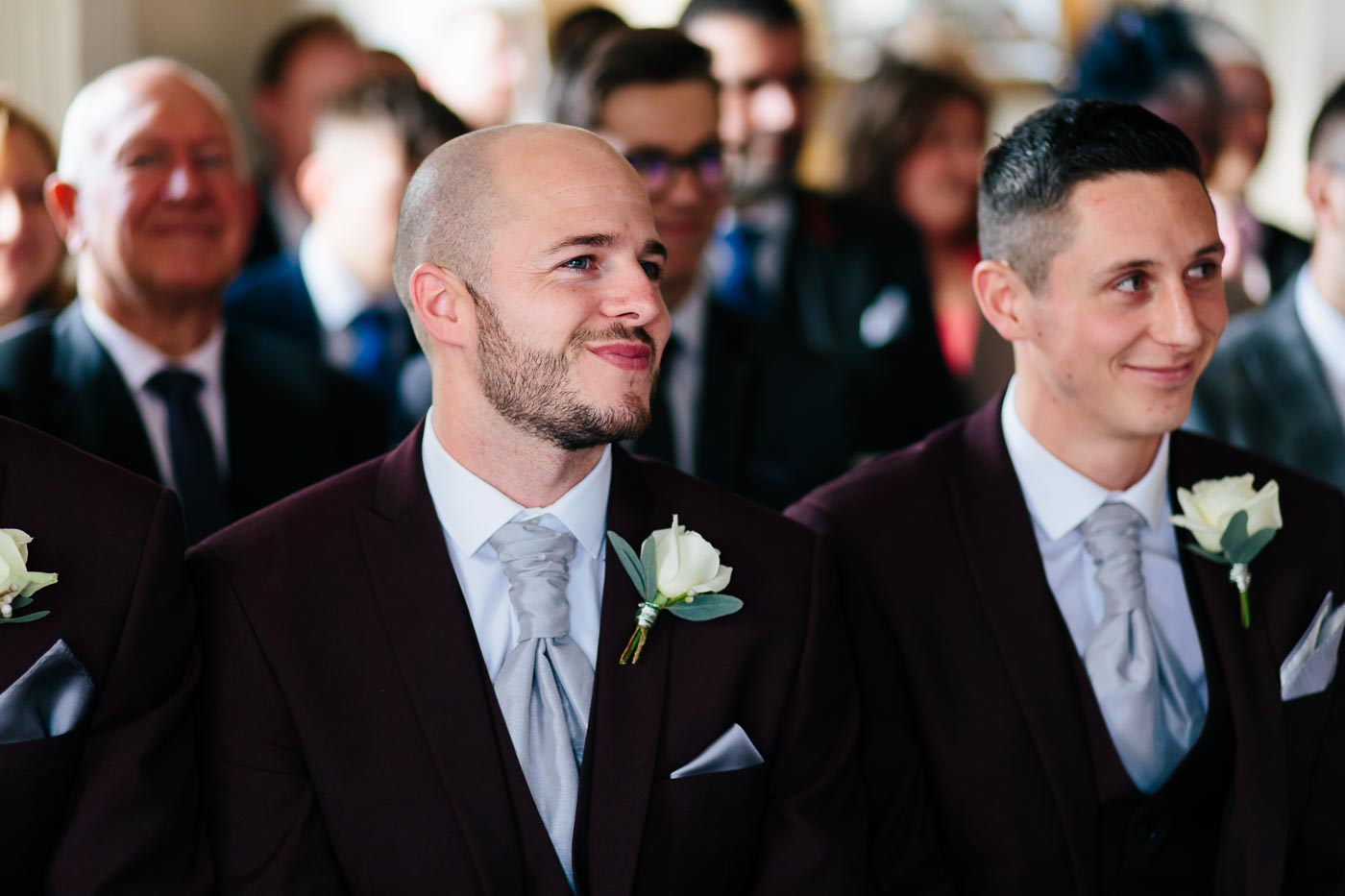one of the groomsmen smiling in the ceremony