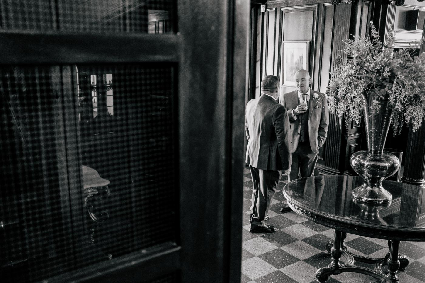 black and white photograph of guests waiting in entrance hall