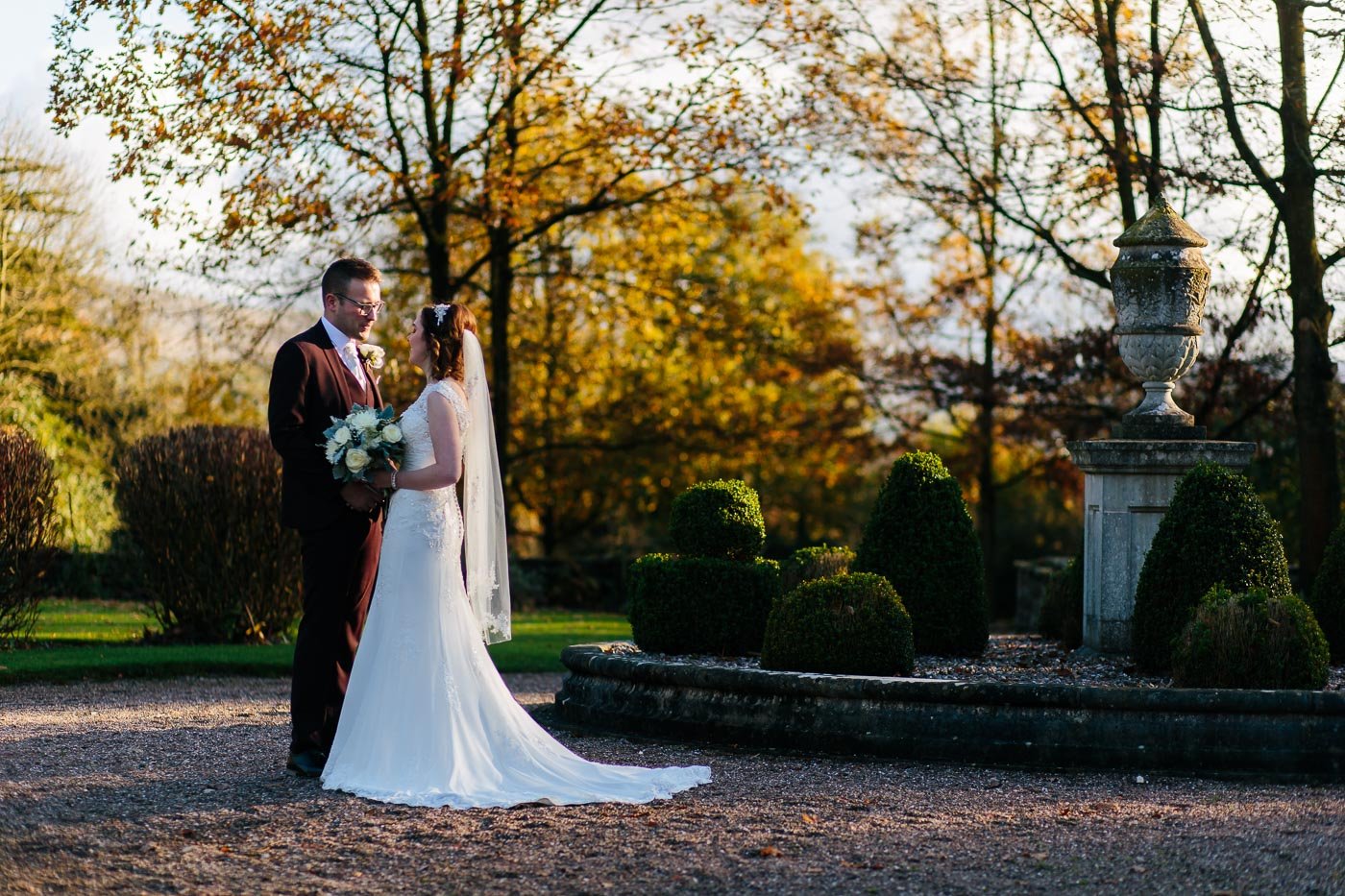 beautiful golden autumn colours in eaves hall gardens with bride and groom