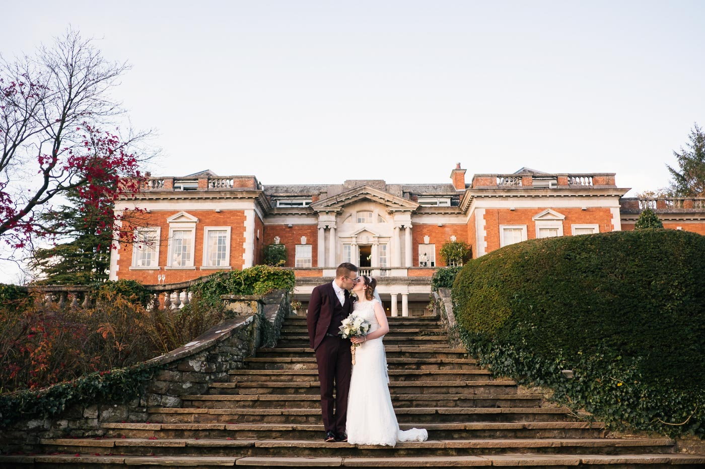 bride and groom portrait at the front of eaves hall