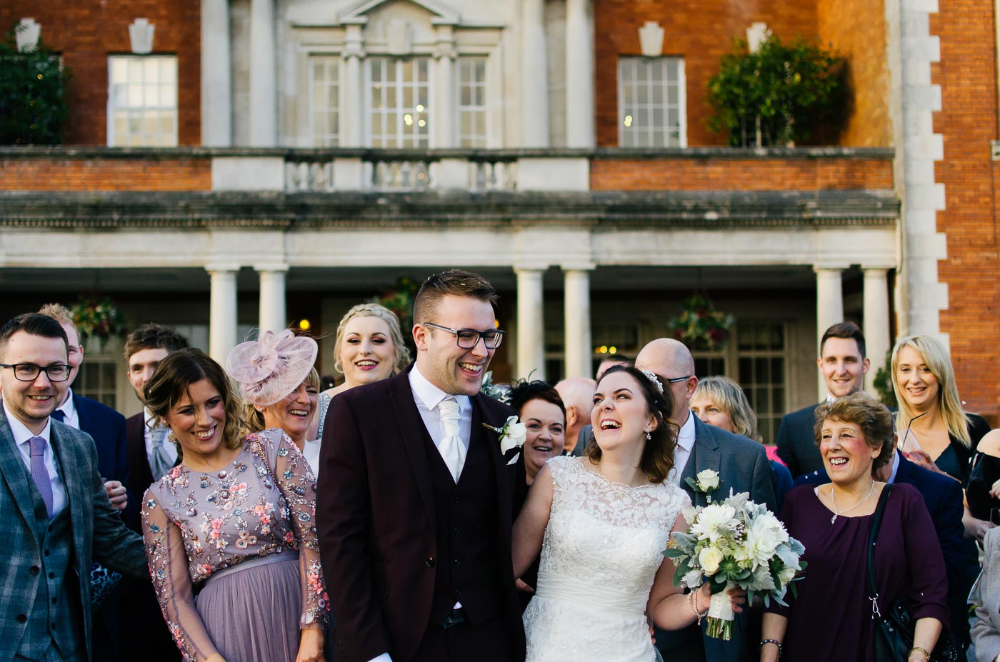bride and groom laughing with guests before the confetti is thrown