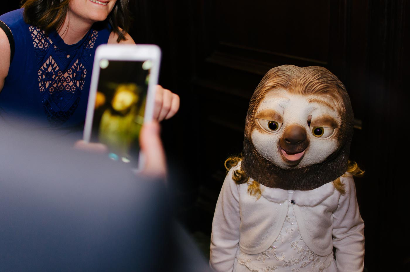 young girl wearing sloth mask using the photobooth