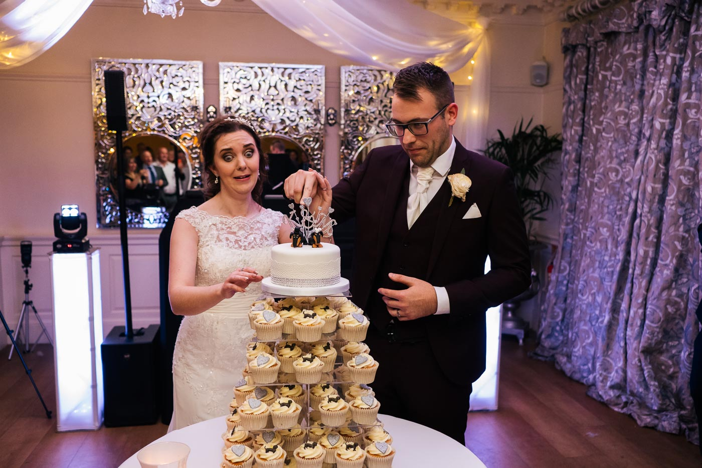 bride pulling funny face as groom cuts the wedding cake