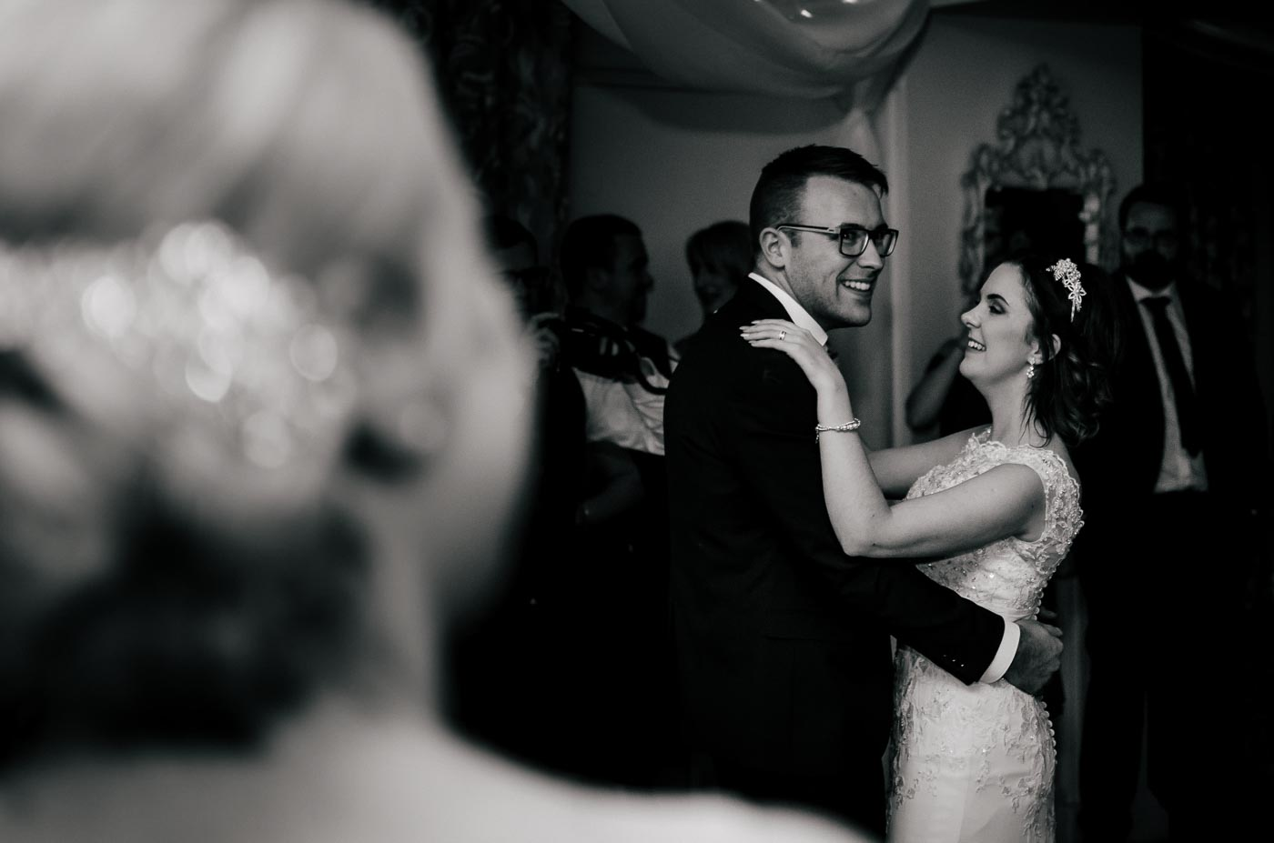 Katie and Matt laughing during the first dance with guests watching