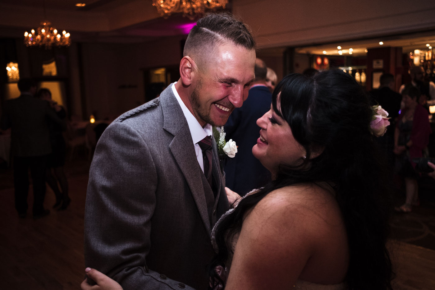 bride and groom laughing when dancing, candid wedding photographs