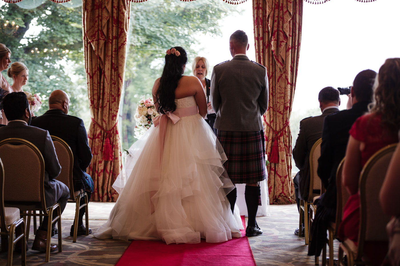 photograph from the back of the room with the bride and groom facing the registrar