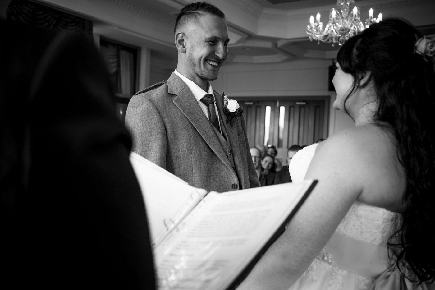 groom smiling at his bride in the wedding ceremony