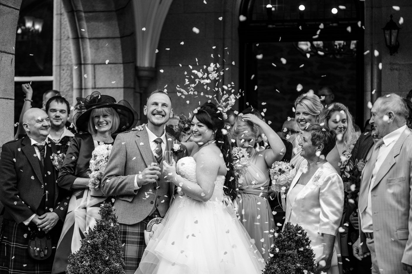 black and white photograph of confetti being thrown at the newly married couple