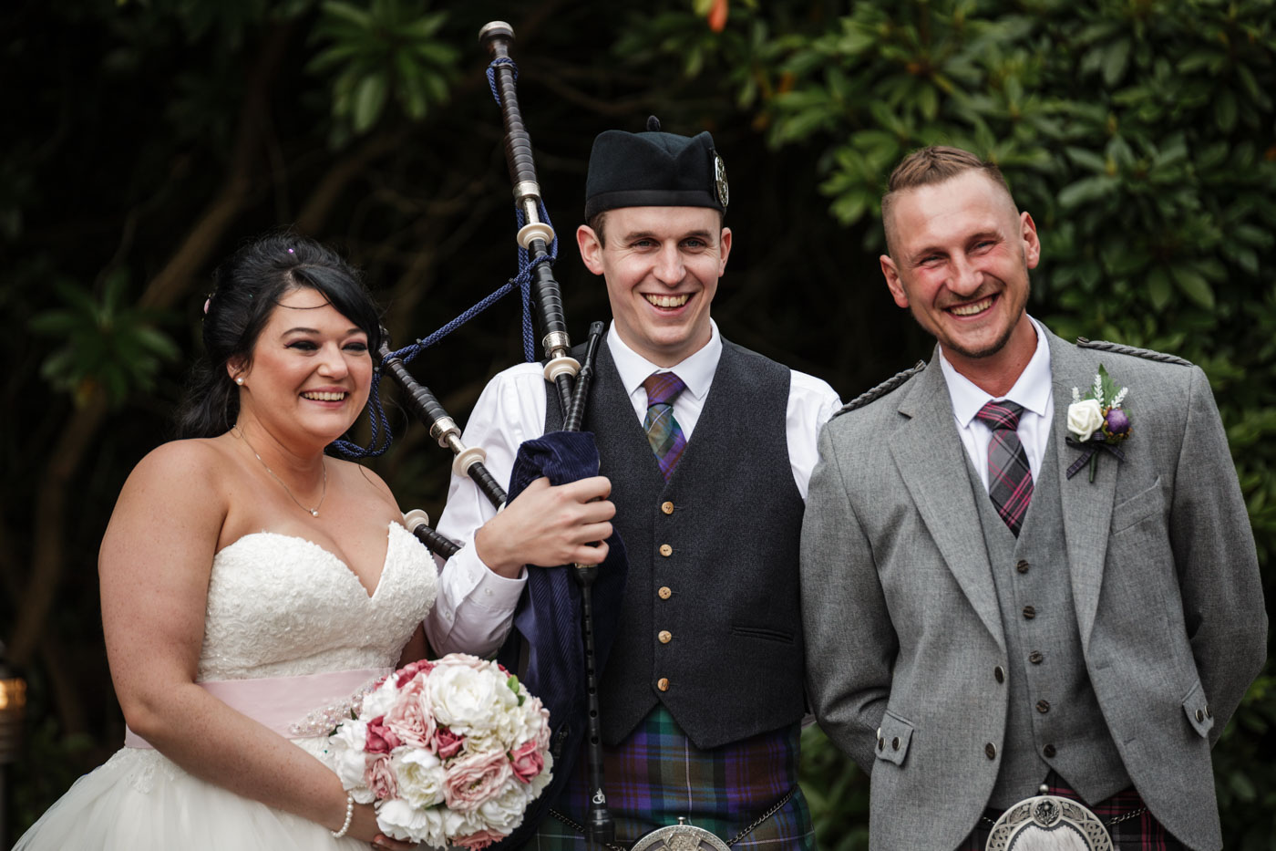bride and groom with bag pipe player