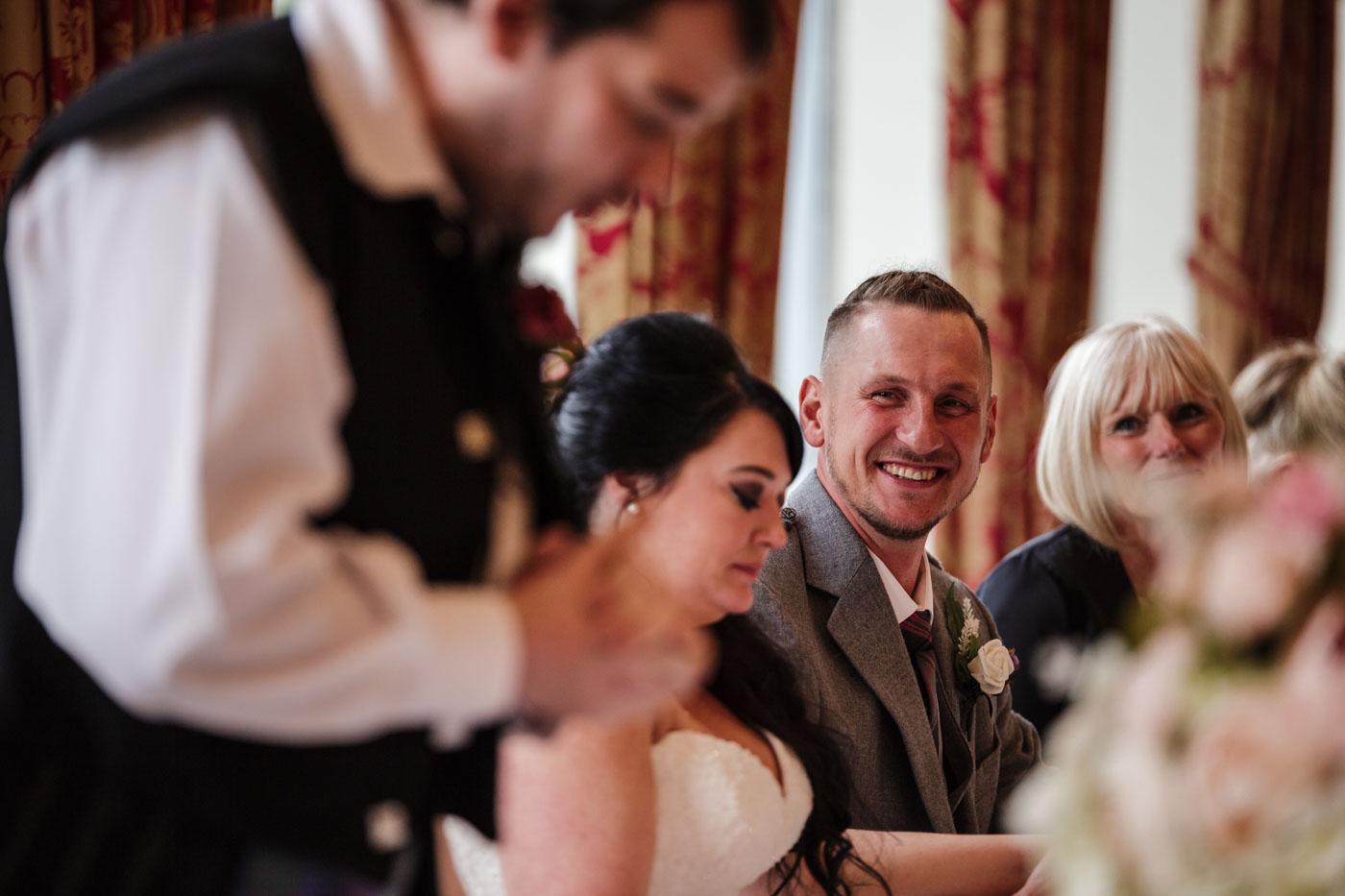 groom smiling at best man speech