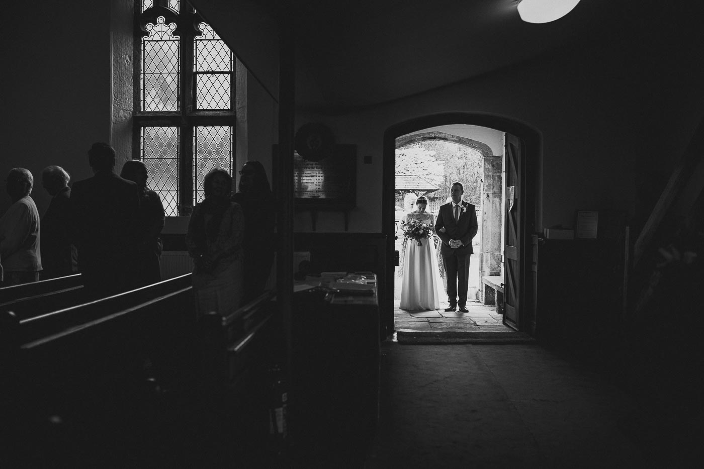 Bride waiting in the church doorway before walking down the aisle, Documentary wedding photographer in Lancashire