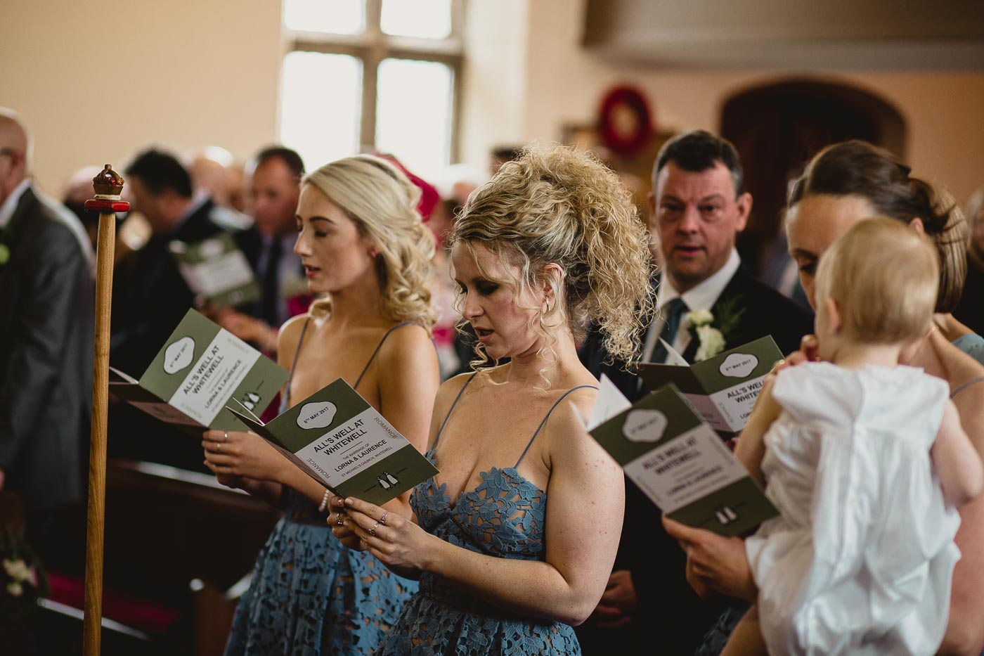 Bridesmaids reading the order of service in church, Natural and relaxed wedding photography