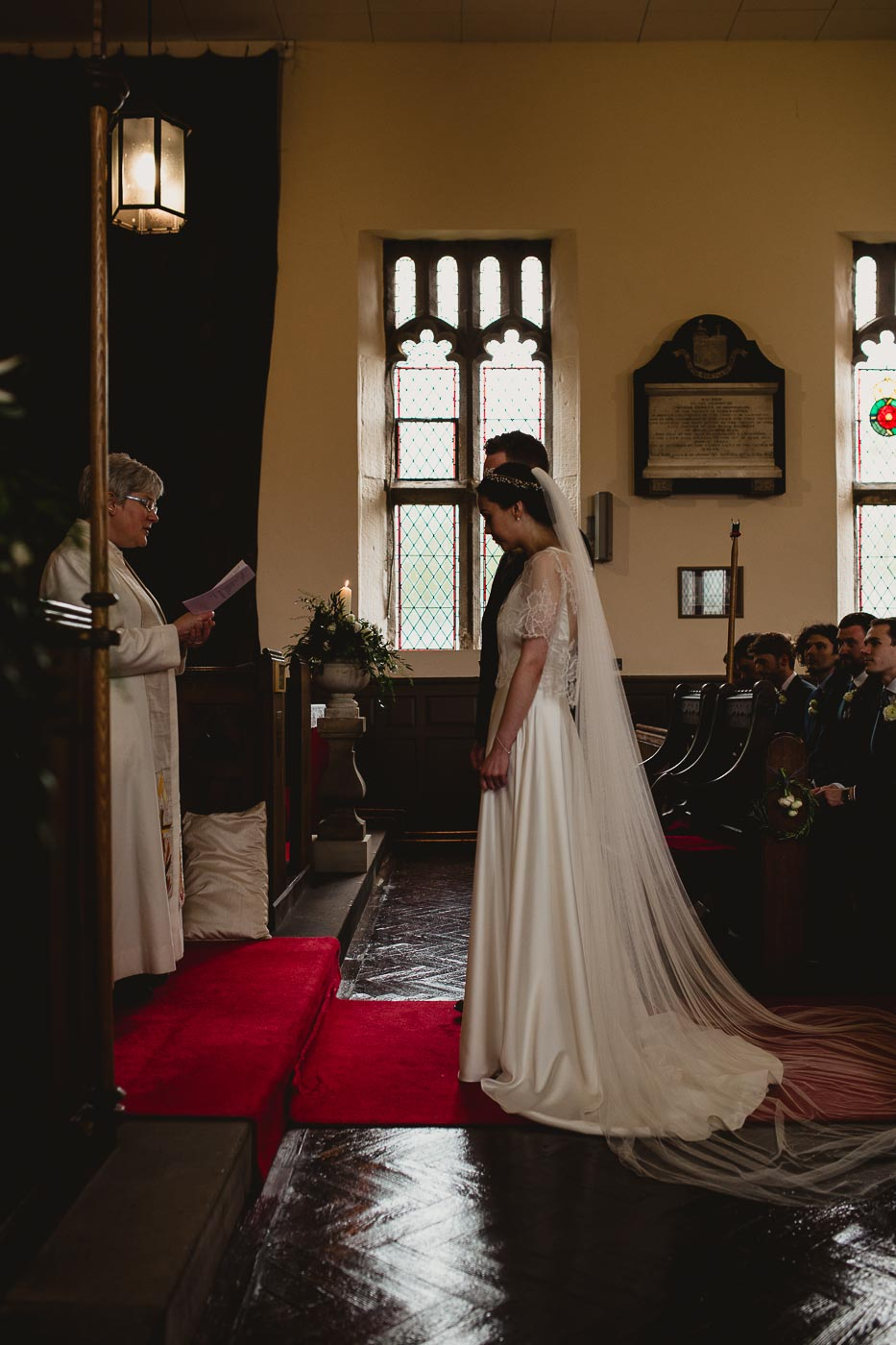Photograph of bride and groom from the side during the church wedding ceremony, Candid wedding photography