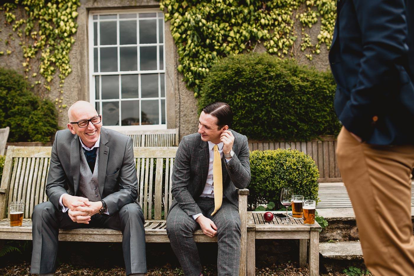 groomsmen sat on a bench at the inn at whitewell wedding venue