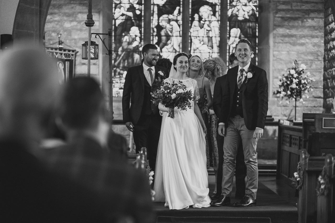Black and white photograph of the bride and groom at front of church moments before walking out, Unposed wedding photographer