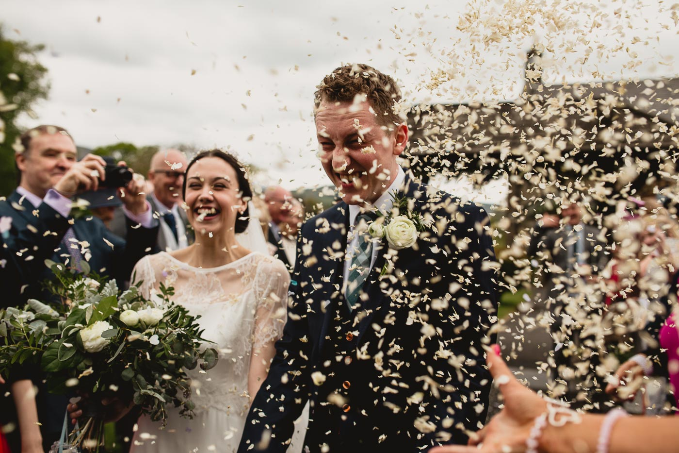 Huge amount of confetti being thrown at the couple just married moments ago, Creative wedding photographer