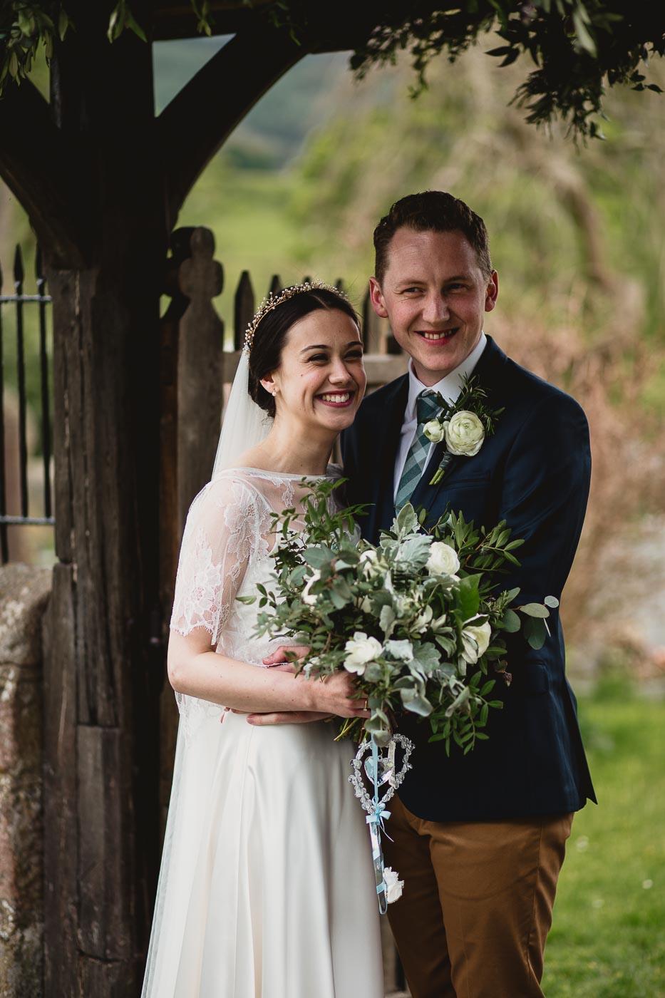 Portrait of the happy couple under church arch with gorgeous bridal bouquet, Wedding Portraits Lancashire