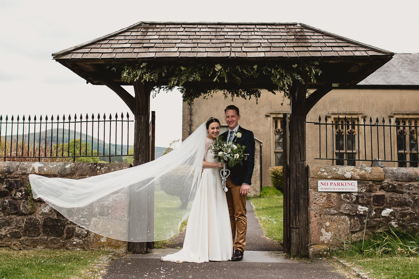 Wedding couple portrait with the brides veil blowing in the wind, No posing wedding photography