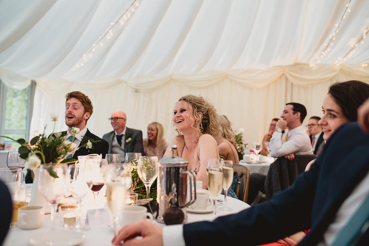 One of the wedding guests laughing at the speeches, Inn at Whitewell wedding venue