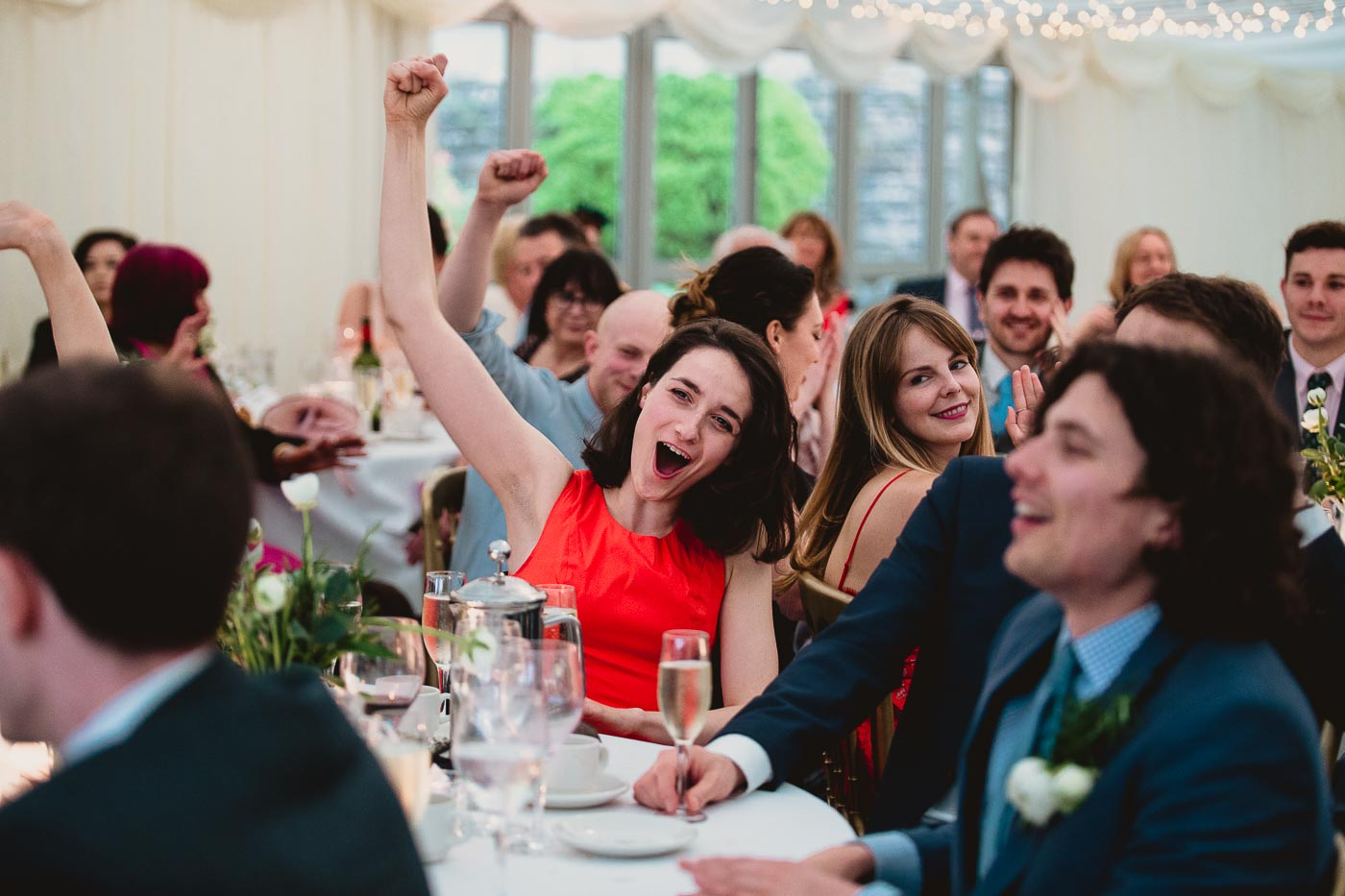 guest fist pumping the air whilst the groom gives wedding speech, Inn at Whitewell