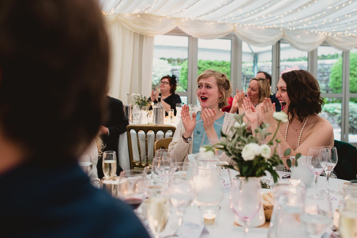 two wedding guests laughing and clapping at the speech, Wedding photography in Lancashire