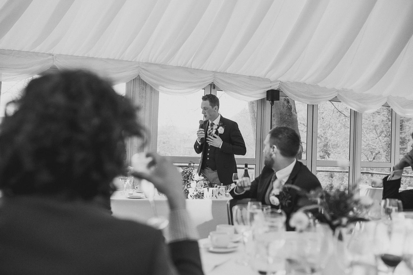 Black and white photograph of the grooms speech in the marquee, Country pub wedding