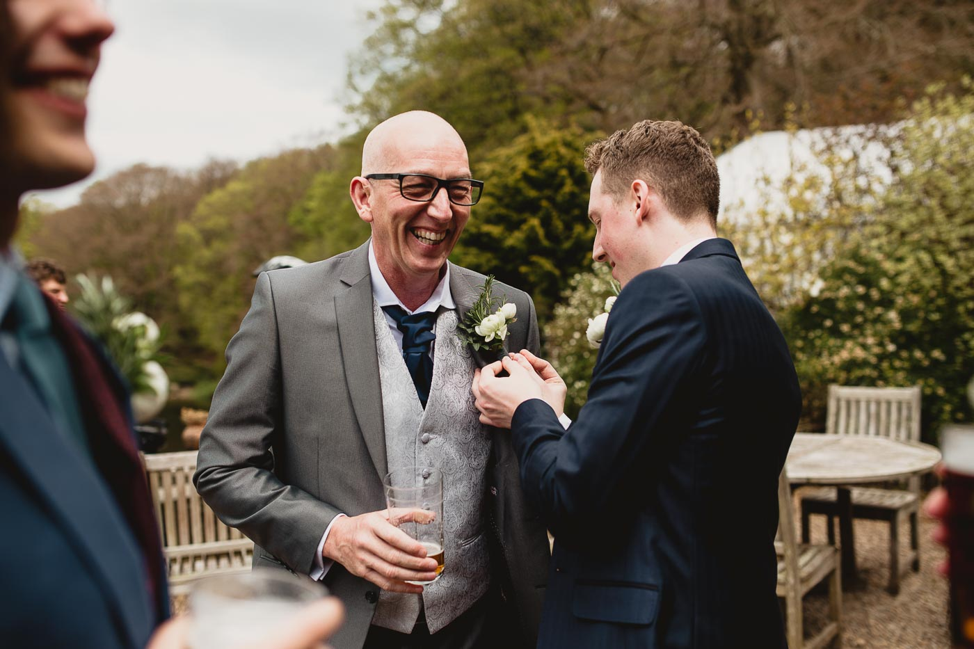groom helping dad with buttonhole on the terrace, real moments wedding photography