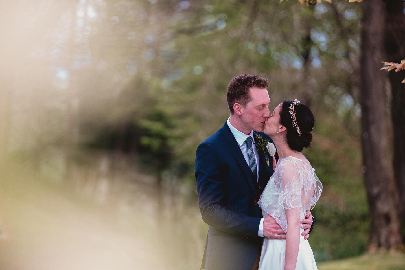 bride and groom kissing for photograph just outside the Inn at Whitewell pub wedding venue