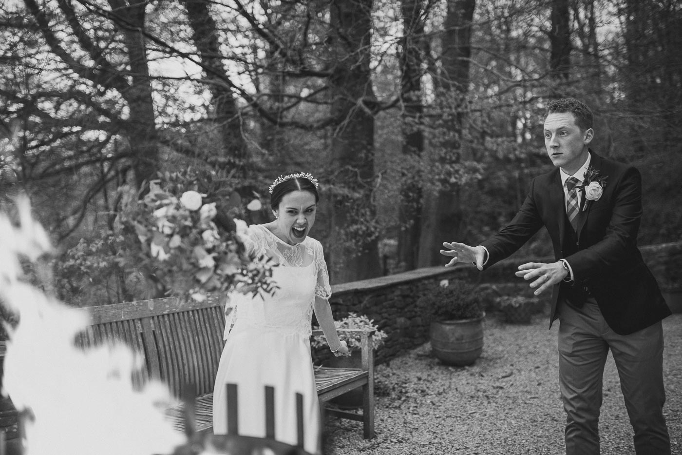 Bride pretending to throw bouquet into the fire outside the marquee