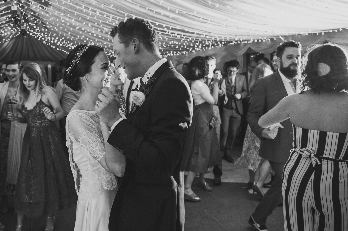 Black and white photograph of bride and groom dancing with fairy lights hanging from the ceiling