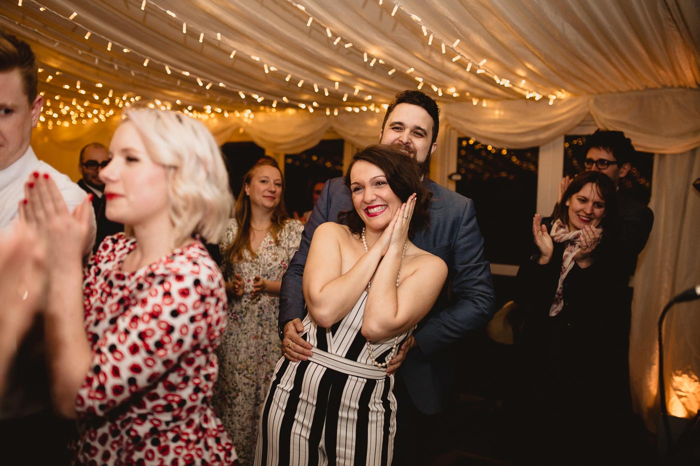 Happy wedding guests smiling as the couple have first dance in marquee wedding venue