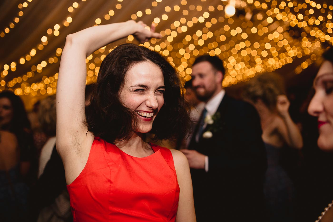 candid photograph of guest dancing wearing red dress