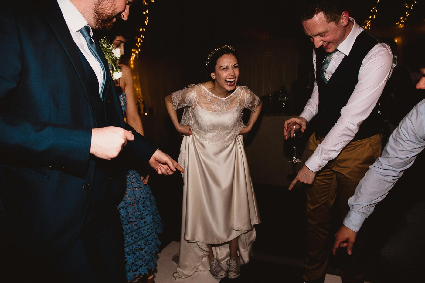 Bride showing her converse wedding trainers to guests, Relaxed Wedding in the Countryside