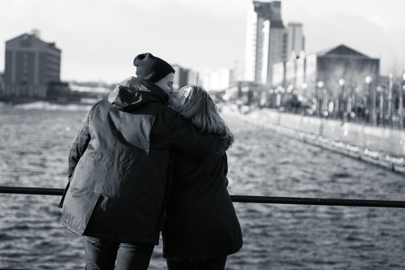 couple kissing overlooking the river near the Lowry