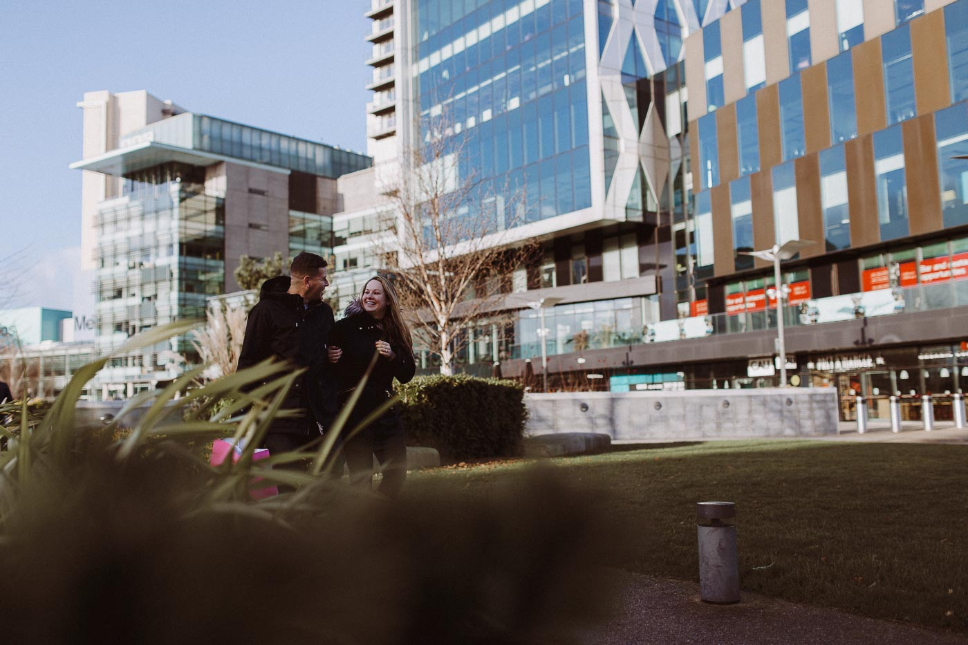 couple laughing and holding hands with media city buildings in the background