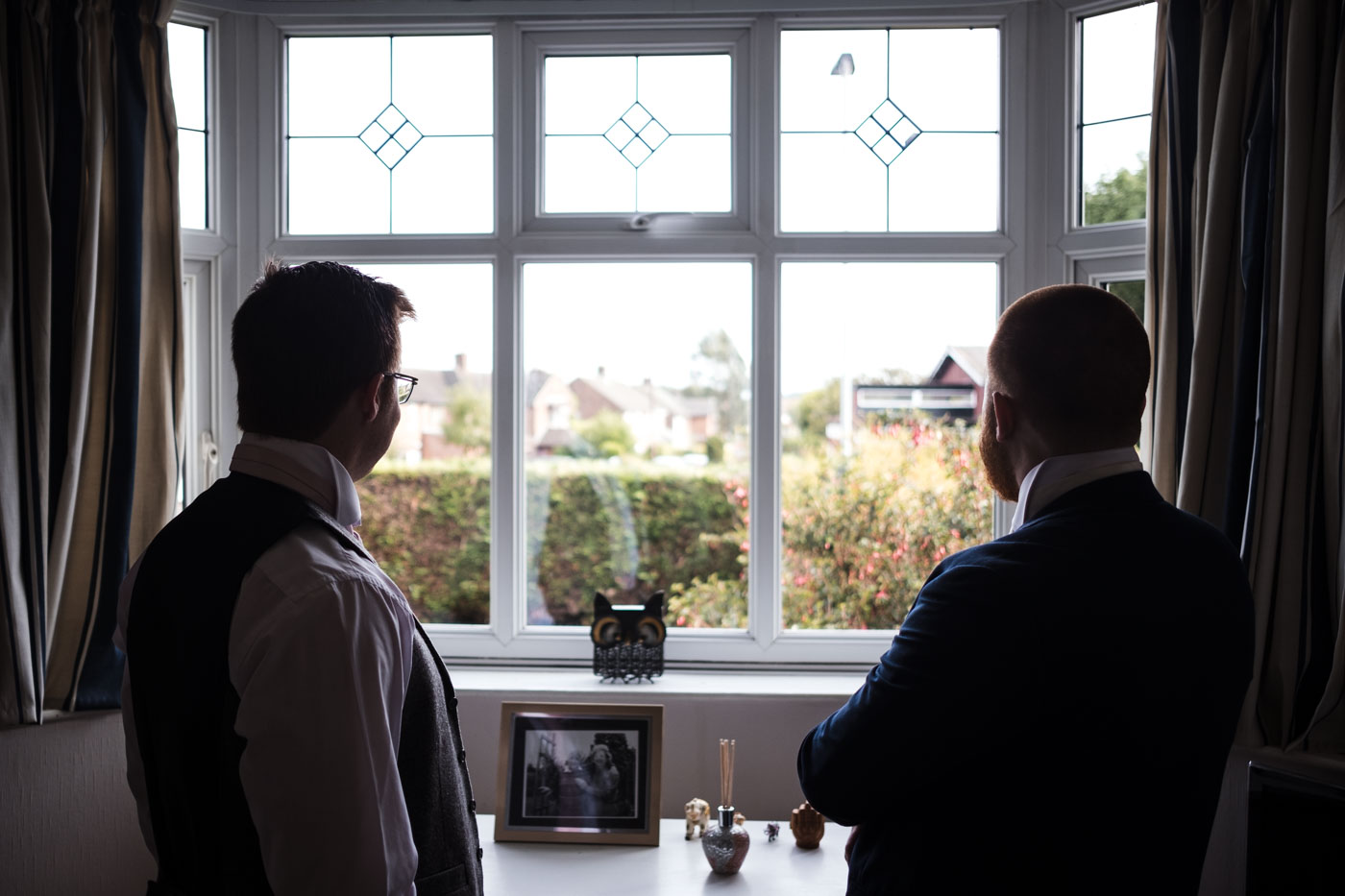 best man and groom looking out of the window